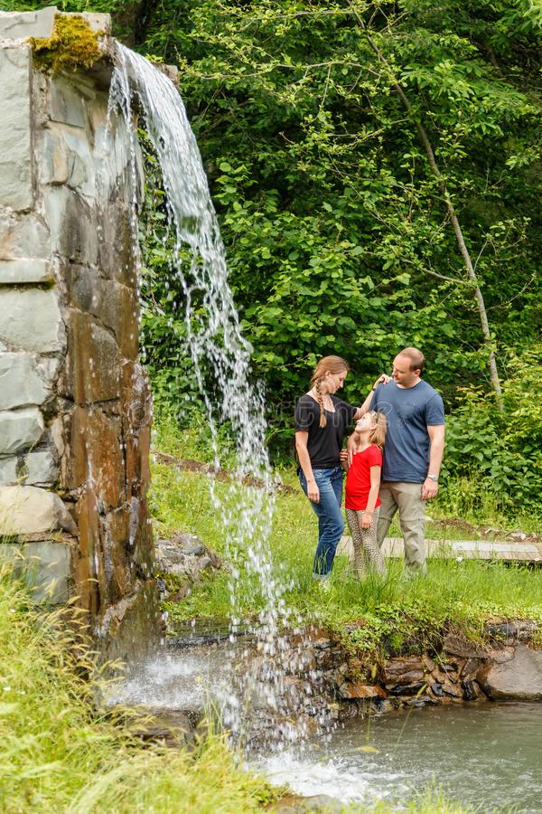 Young happy Caucasian family of father, mother and daughter stand together in sunny summer mountain forest near waterfall royalty free stock photo