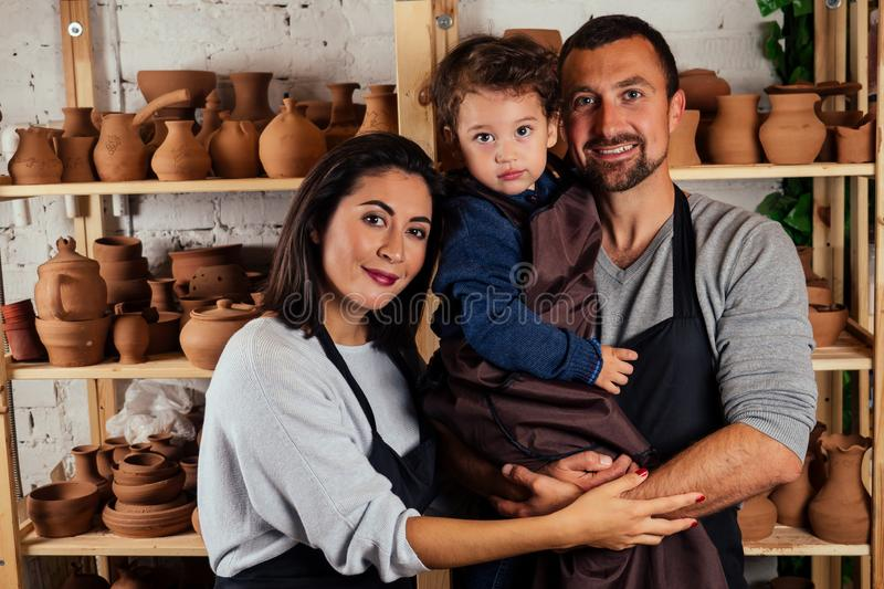 Young happy caucasian family with son working on potter shop .beautiful mother with dad and little boy making ceramic stock images