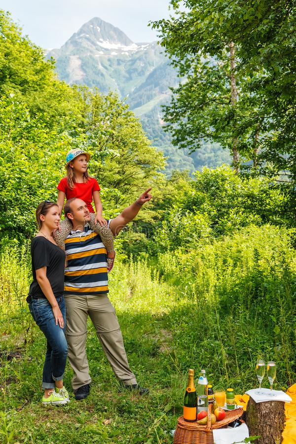 Young happy Caucasian family of three people having picnic in summer mountain forest on Caucasus mountain peak background royalty free stock photography