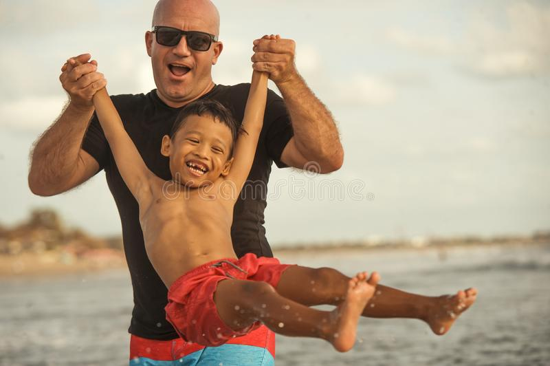 Young happy Caucasian man and his mixed Asian ethnicity young son at tropical beach Summer holidays the child lift on air by his stock images