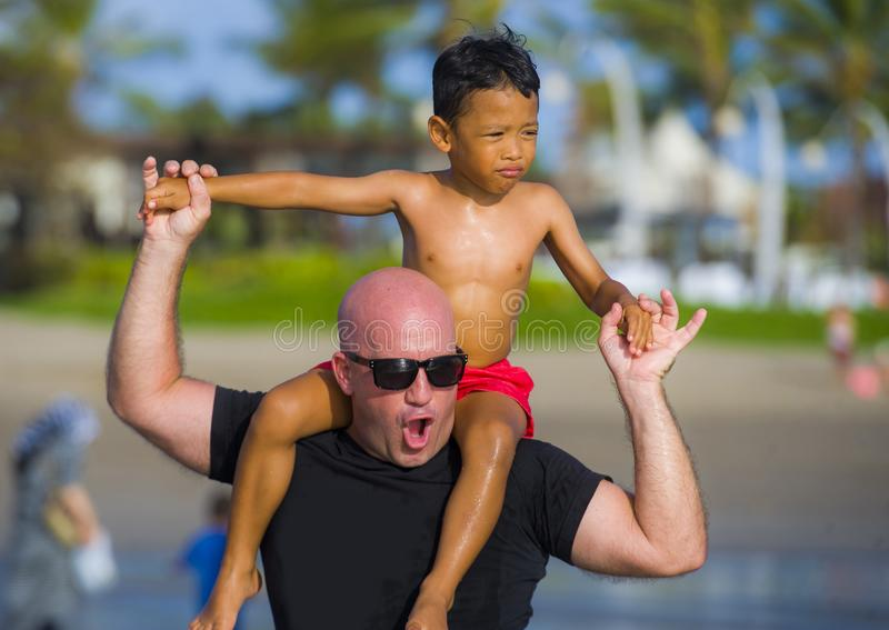 Young happy Caucasian man and his mixed Asian ethnicity young son at tropical beach Summer holidays the child sitting on his stock photo