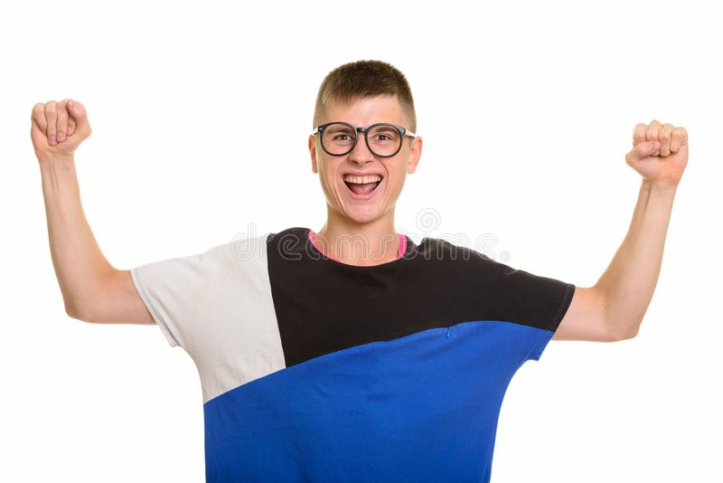 Young happy Caucasian nerd man smiling and looking motivated wit. H both arms raised royalty free stock image