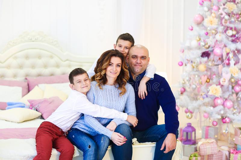 Young happy caucasian parents sitting with sons near fir tree on bed. stock photos