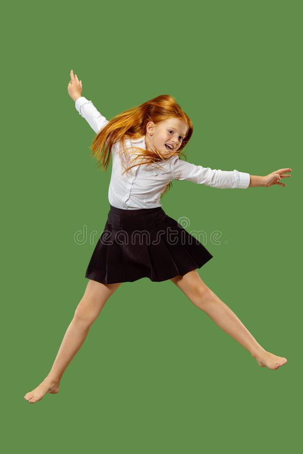 Young happy caucasian teen girl jumping in the air , isolated on green background royalty free stock photo