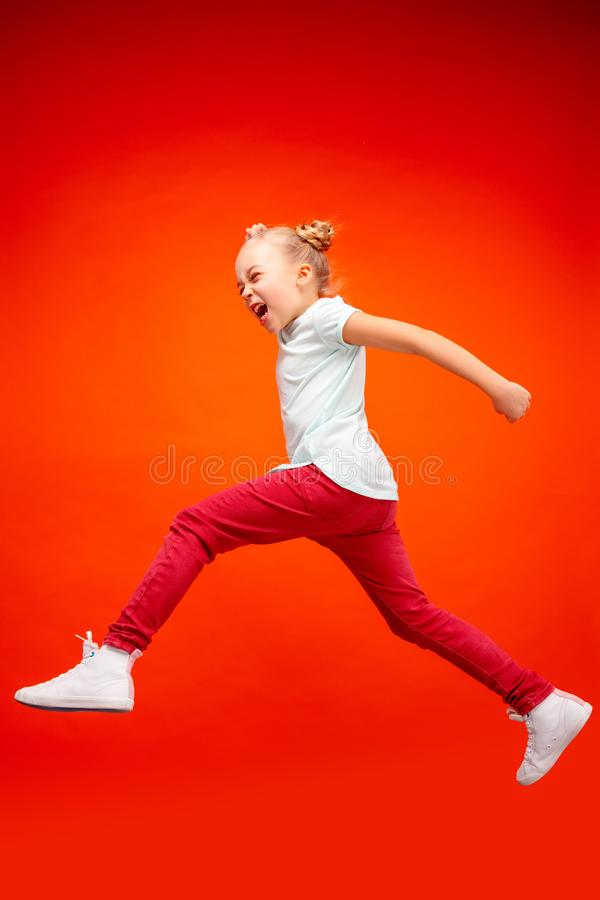 Young happy caucasian teen girl jumping in the air, on red studio background. royalty free stock photos