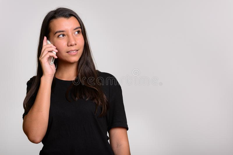 Young happy Caucasian woman smiling and talking on mobile phone stock photography