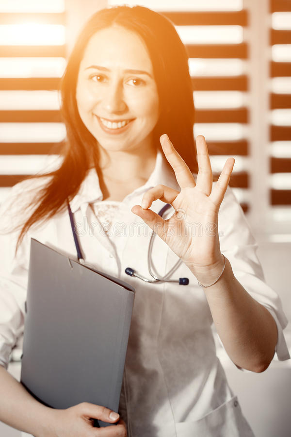 Young happy cheerful doctor in white uniform gesturing ok stock photo