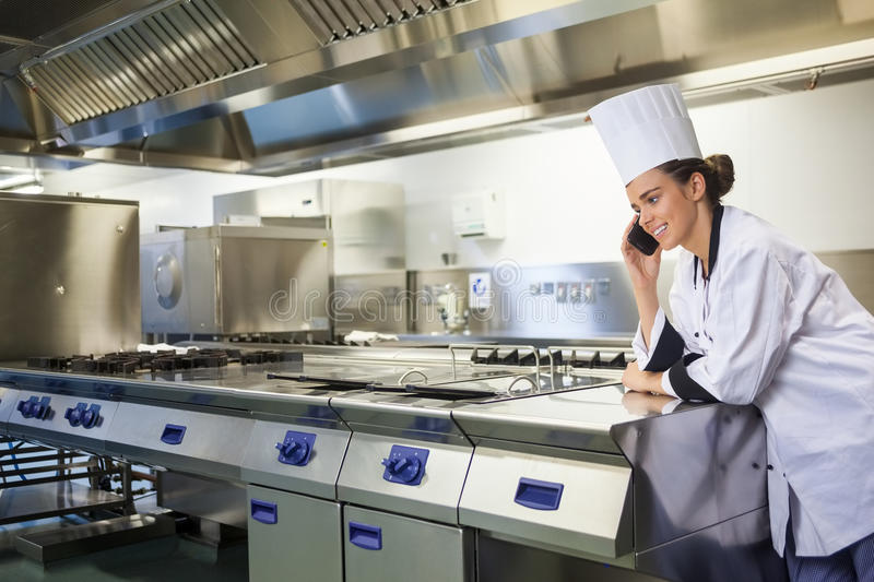 Young happy chef standing next to work surface phoning royalty free stock photography