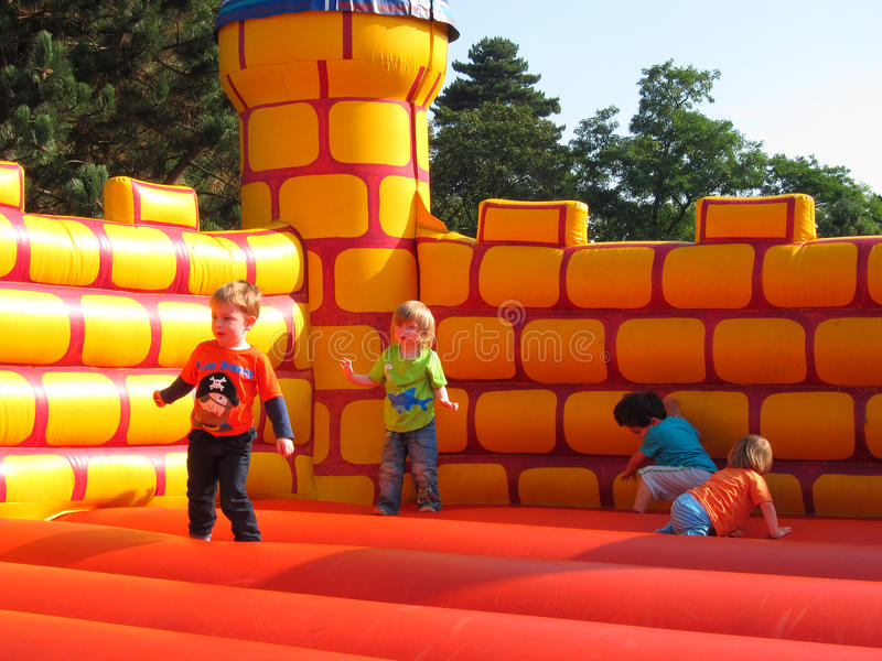 Young happy children playing, jumping,bouncy castl stock images