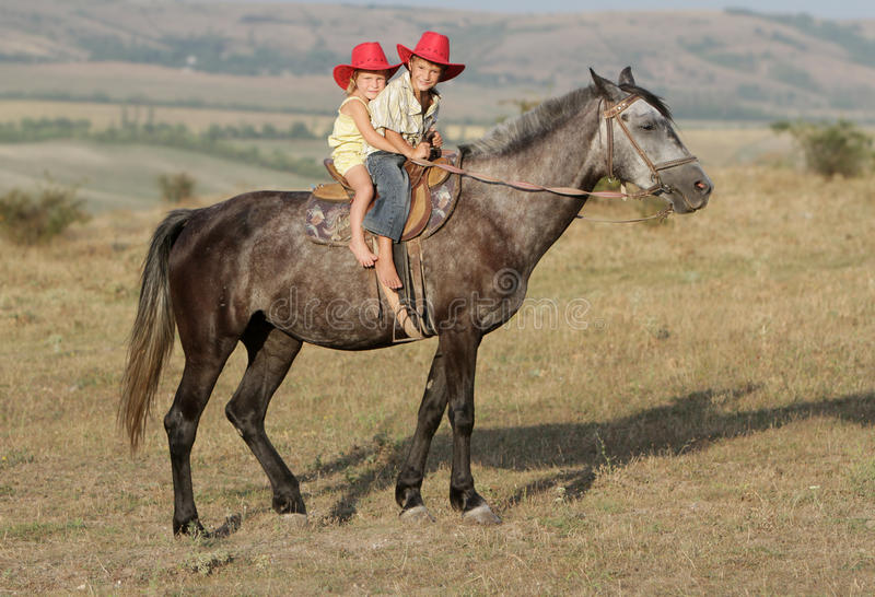 Young happy children riding horse royalty free stock images