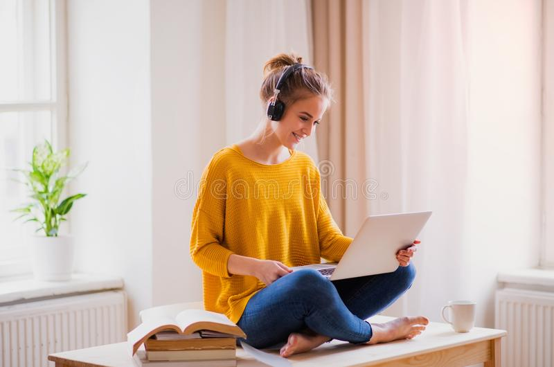 A young female student sitting at the table, using headphones when studying. A young happy college female student sitting at the table at home, using headphones royalty free stock photography