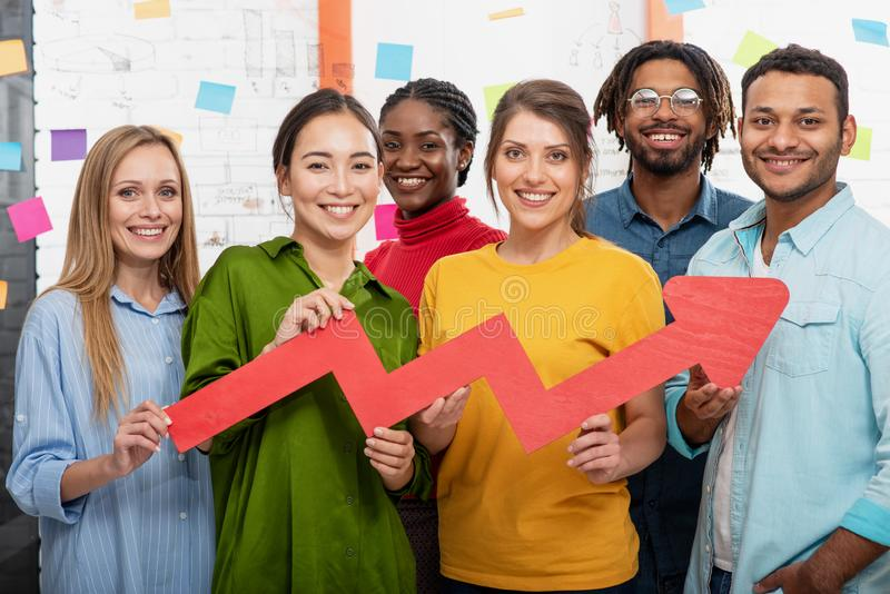 Young happy and colorful business team hold a red statistical arrow. Concept of growing, succesful and profit. Young happy and colorful business team in office stock image
