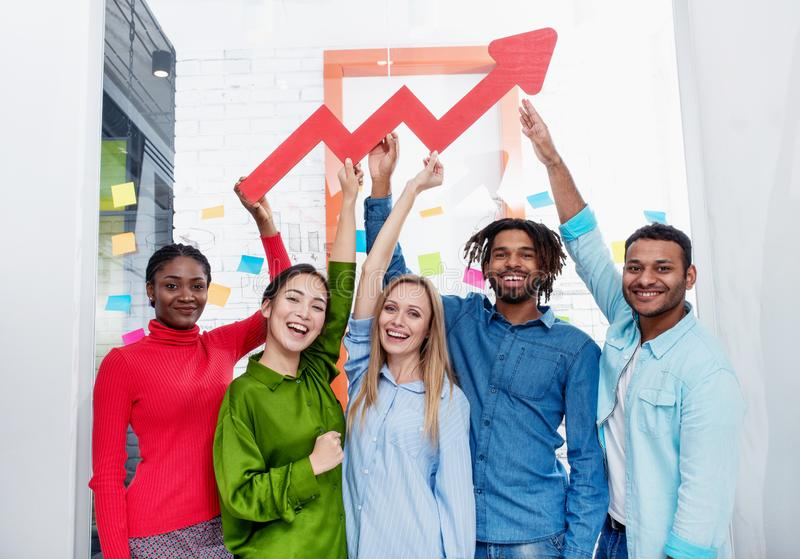 Young happy and colorful business team hold a red statistical arrow. Concept of growing, succesful and profit royalty free stock images