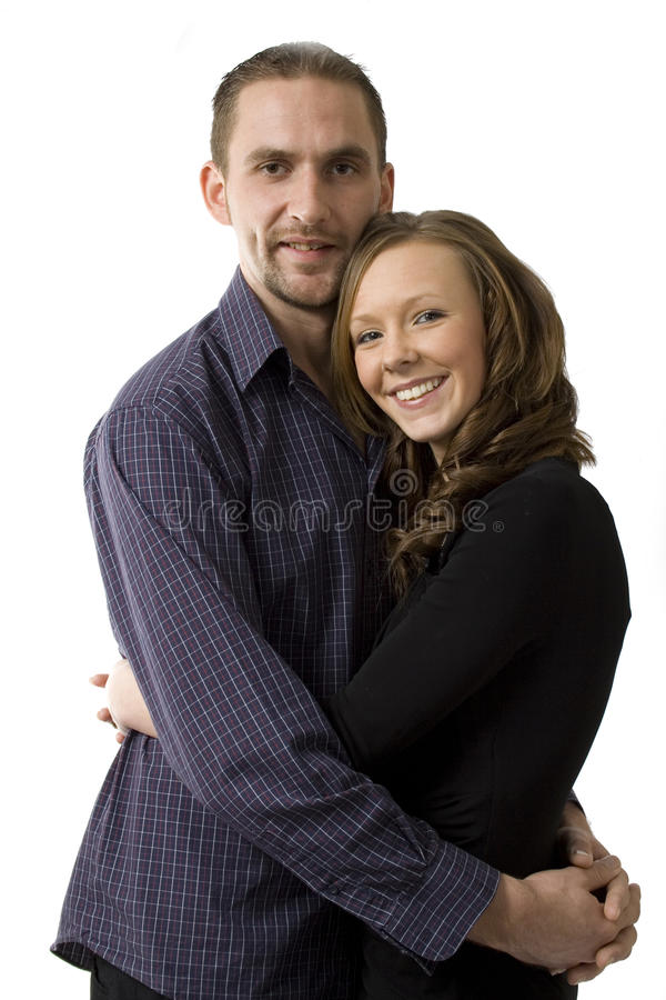 Young happy couple. Posed in a close hug with arms around each other stock photo