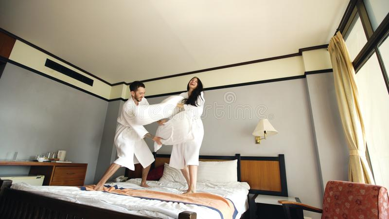 Young Happy Couple In Bathrobe Fight Pillows On Bed Hotel During Their Honeymoon