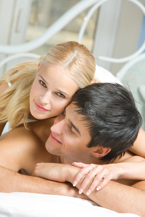 Young happy couple in bedroom royalty free stock photos