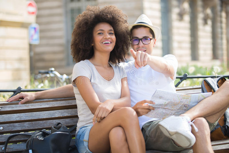 Young happy couple on bench at park. Young happy couple on a bench at the park royalty free stock image
