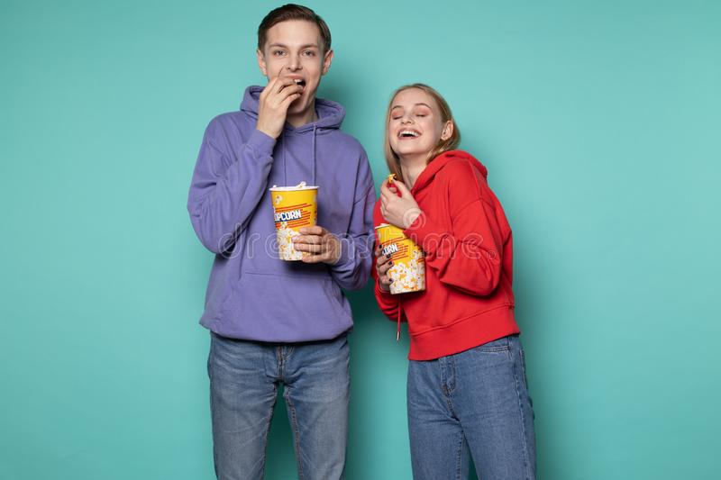 Young happy couple in casual clothes standing isolated over blue background royalty free stock photos