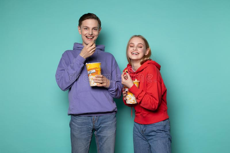 Young happy couple in casual clothes standing isolated over blue background stock image