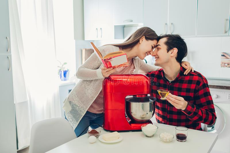 Young happy couple cooking on kitchen with food processor. Woman and man reading recipe and hugging stock photos