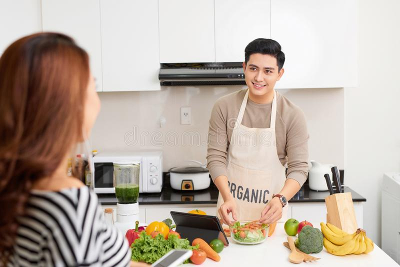 Young happy couple cooking together in the kitchen at home royalty free stock images