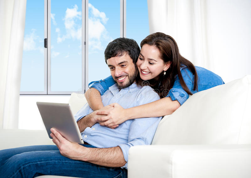 Young happy couple on couch at home enjoying using digital tablet royalty free stock photo