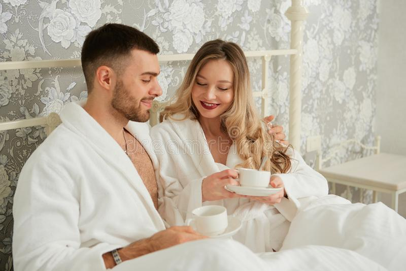 Young happy couple drink coffee in luxury hotel room stock image