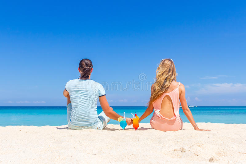 Young happy couple enjoying tropical cocktails on sand beach stock images