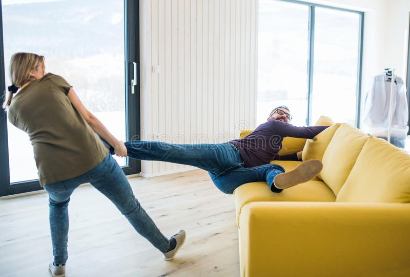 A young couple moving in new home, having fun. stock photography