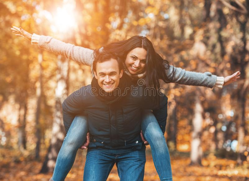 Young Happy Couple Have Fun in Park in Autumn. stock photos