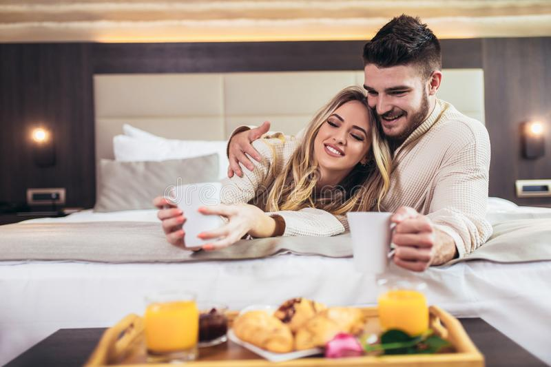 Happy couple having breakfast in luxury hotel room royalty free stock images