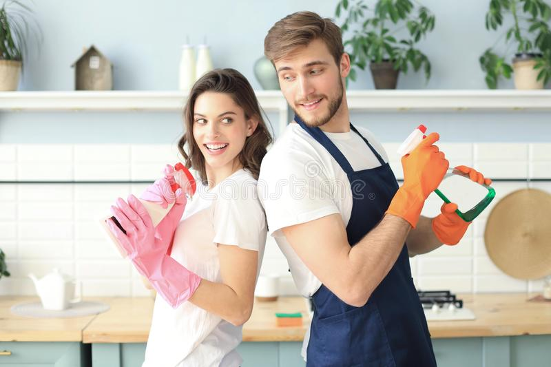 Young happy couple is having fun while doing cleaning at home.  stock photo