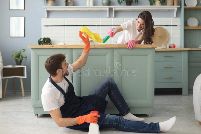 Young happy couple is having fun while doing cleaning at home.  royalty free stock photo