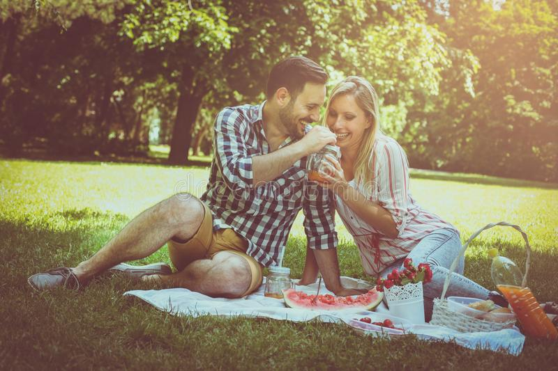 Young happy couple having picnic in the meadow. Couple sitting o royalty free stock photos