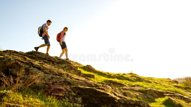Young Happy Couple Hiking with Backpacks on the Beautiful Rocky Trail at Sunny Evening. Family Travel and Adventure. Couple of Young Happy Travelers Hiking with