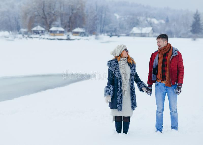 Young happy couple is holding hands and joyfully talking while walking along the snowy countryside. royalty free stock photography