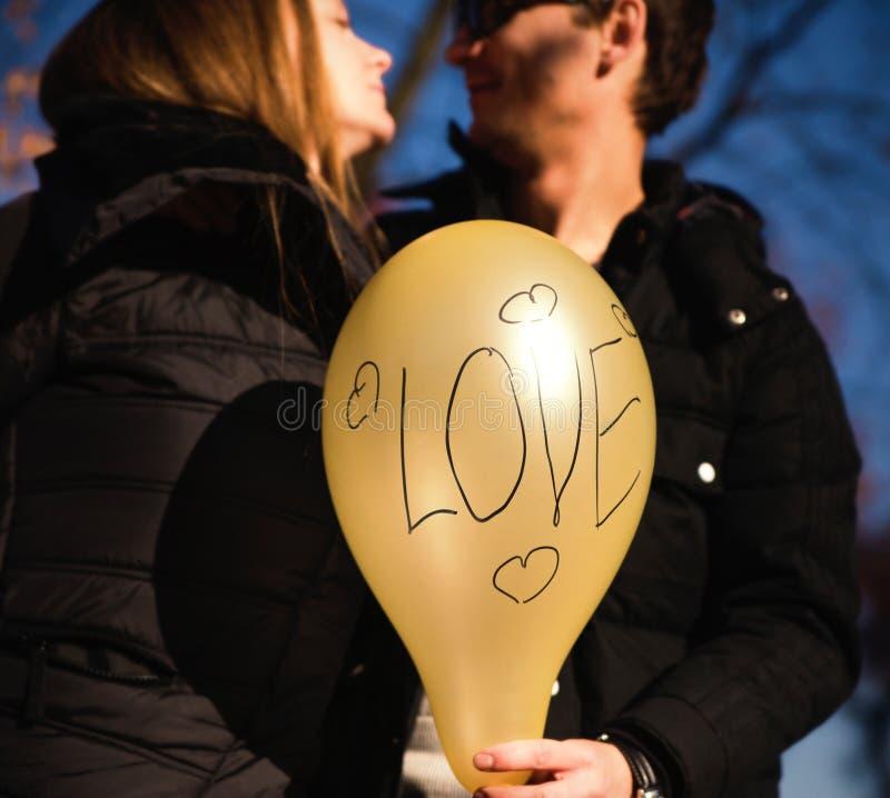 Young happy couple holding yellow balloon stock image