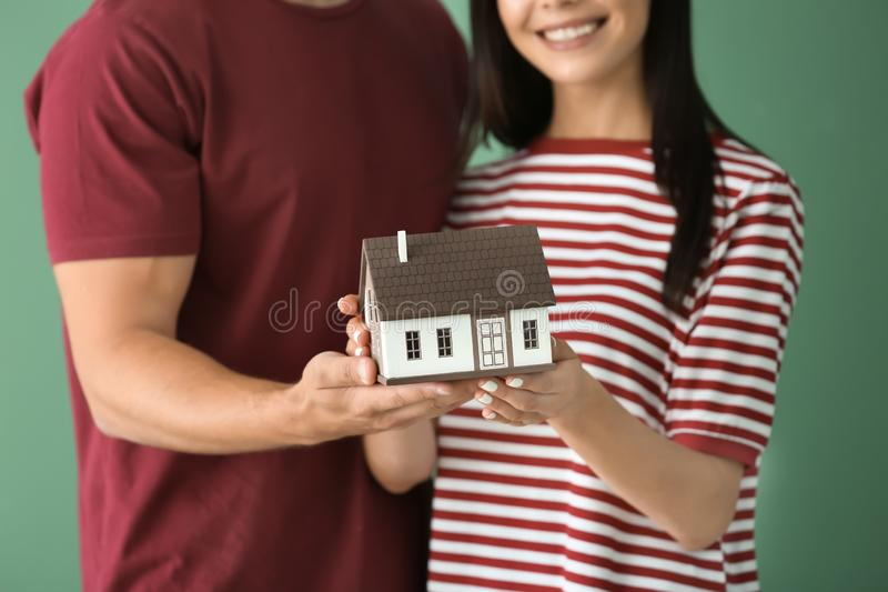 Young happy couple with house model on color background stock photography