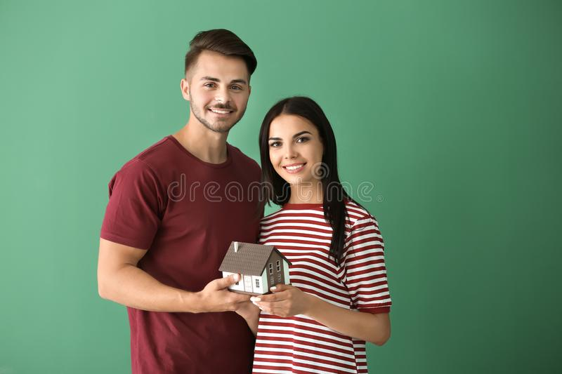 Young happy couple with house model on color background royalty free stock image