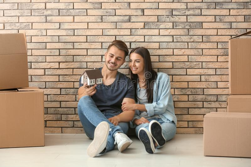 Young happy couple with house model and moving boxes sitting on floor at new home royalty free stock photo