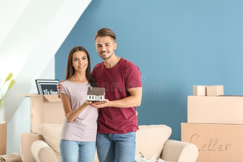Young happy couple with house model at new home royalty free stock photo