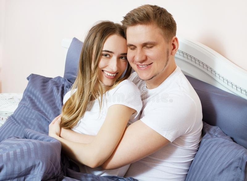 Young happy couple hugging in bed, family in bedroom after sleep, weekend.  stock photo
