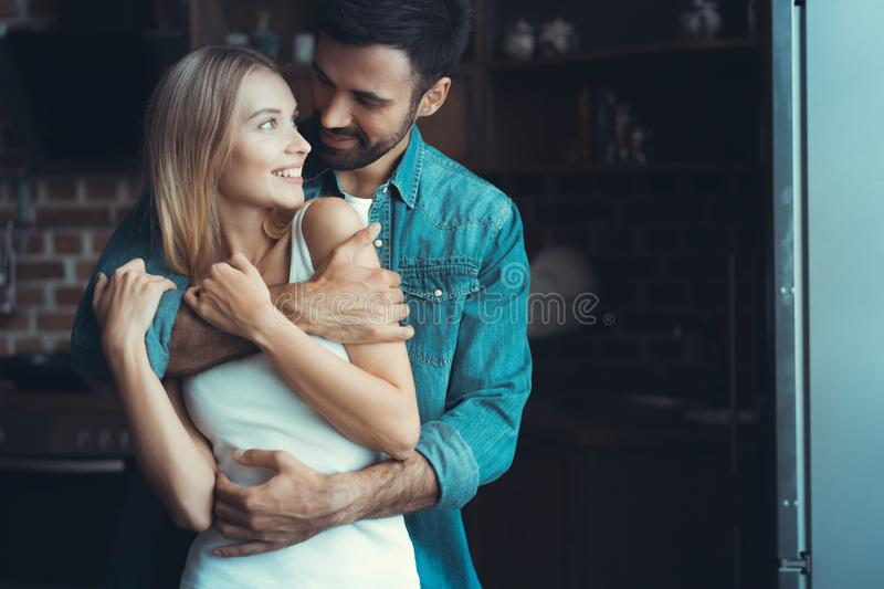 Young happy couple hugging and looking at each other in the interior of a new kitchen, happiness in a new home. Young happy couple hugging and looking at each royalty free stock image