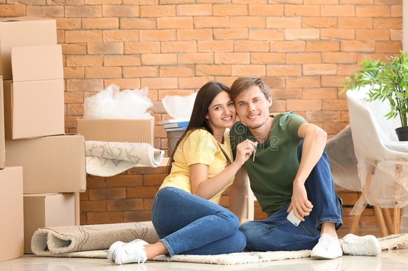 Young happy couple with key and moving boxes sitting on carpet at new home royalty free stock image