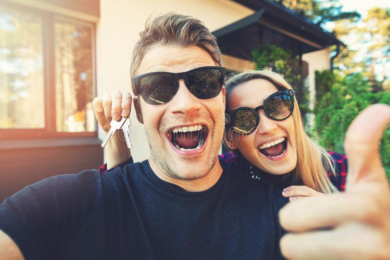 Young happy couple with keys in hand standing outside of their new home royalty free stock photos