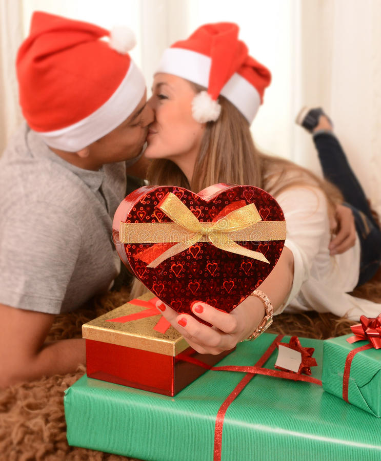 Young Happy Couple Kissing on rug at Christmas royalty free stock image