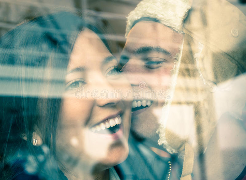 Young happy couple in love at the beginning of a Love Story. Fashion men whispers a soft kiss in the ear of the loved young woman stock image