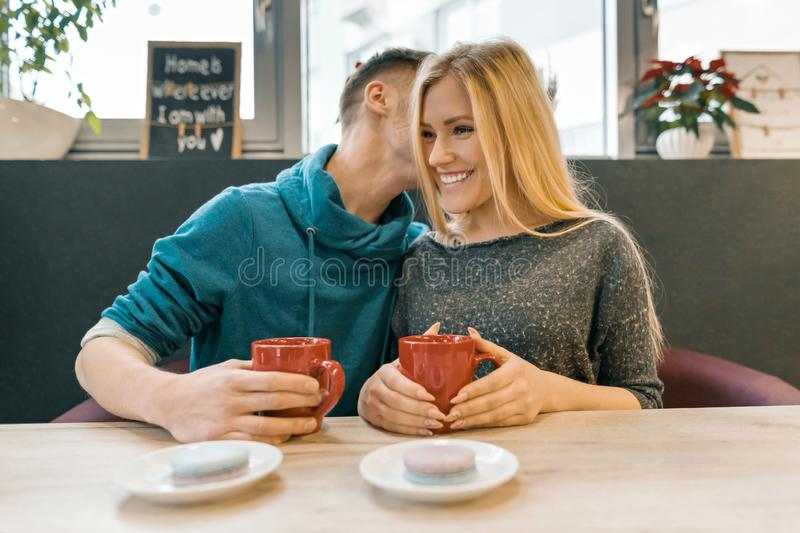 Young happy couple in love in cafe, young man and woman together smile hugging drink coffee tea royalty free stock photo