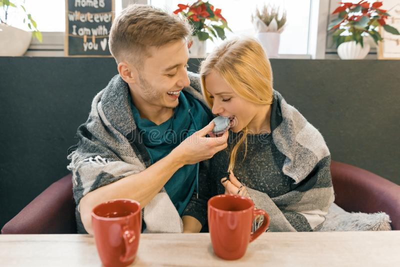 Young happy couple in love in cafe, young man and woman together smile hugging, drinking coffee tea eating macaroons royalty free stock image