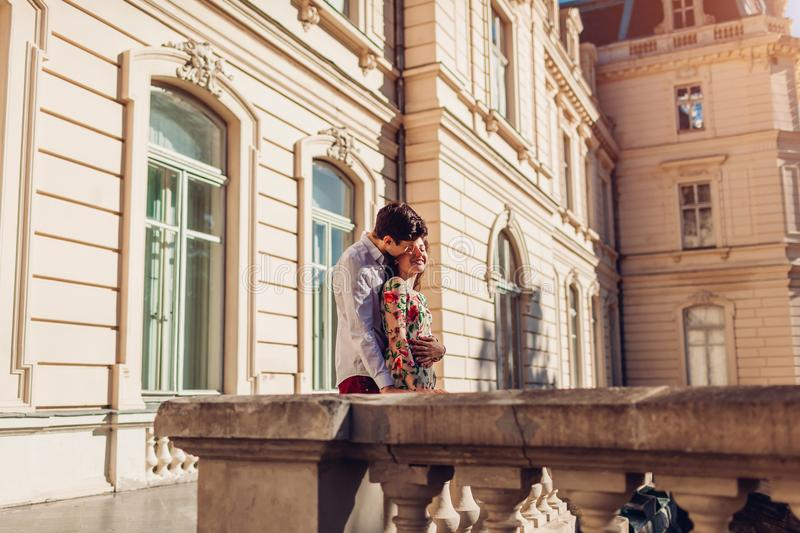 Young happy couple in love hugging outdoors. Romantic man and woman walking by old city architecture royalty free stock photography